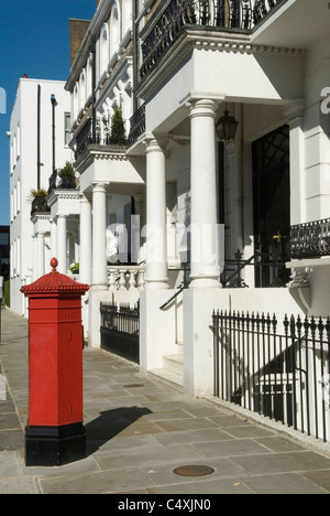 Georgian housing London traditional red pillar letter box. Pembroke Gardens London W8. Borough of Kensington and - Stock Photo
