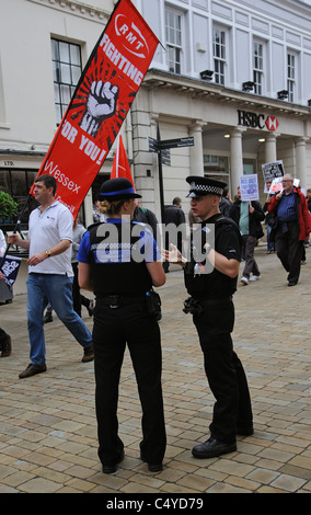 Police officers on duty as Trade Unionists protesting against public service cuts march in Winchester on the Upper - Stock Photo
