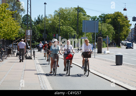 Girls cycling at Østerport in the city of Copenhagen on one of the many bicycle paths along the city streets. Copenhagen, - Stock Photo