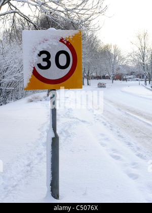 A snow covered speed limit sign. - Stock Photo