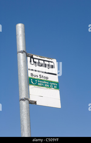 Bus stop sign on metal post showing services by traveline cymru in Cowbridge, vale of Glamorgan, Wales - Stock Photo