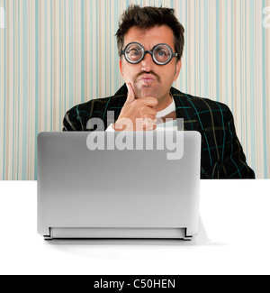 Nerd pensive man glasses silly expression laptop computer thinking a solution - Stock Photo