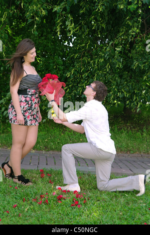 A young man on his knees gives a girl a dozen roses and makes an offer, Moscow, Russia - Stock Photo