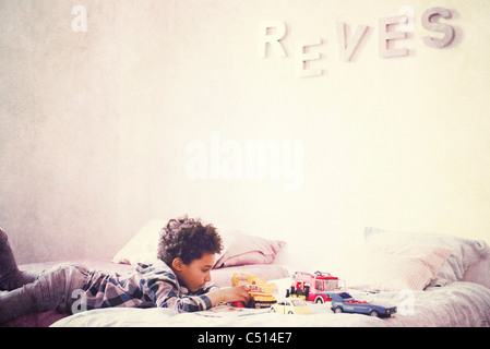 Little boy lying on stomach on bed playing with toy cars - Stock Photo