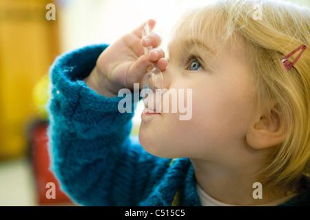 Baby girl feeding herself with spoon - Stock Photo