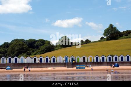 Broadsands beach,Beachhuts and green fields, BOATS, BLUE, SEA, SKY, SEASIDE, SCENE, SEASHORE, BATHERS, COASTAL,Family - Stock Photo