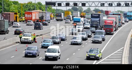 M25 motorway Essex police car arrives at scene of car accident below bridge Highways Agency clearing debris traffic - Stock Photo