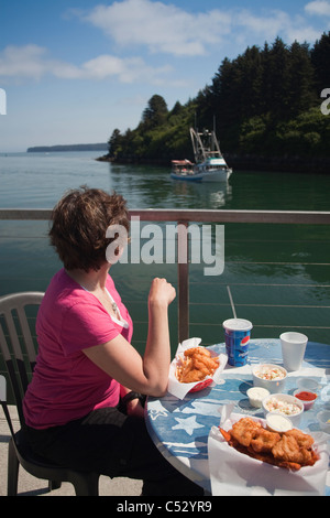 Woman watching and eating a seafood lunch at the Channel Side Chowder House in Kodiak, Kodiak Island, Alaska - Stock Photo