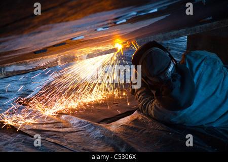 Worker cuts metal fittings off a boat hull, Kodiak Boatyard, Saint Herman Harbor, Kodiak, Near Island, Alaska - Stock Photo