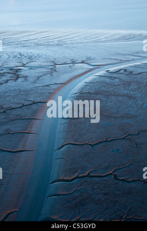 Aeral evening view of patterns in the mud flats of Cook Inlet near the Drift River, Southcentral Alaska, Winter - Stock Photo