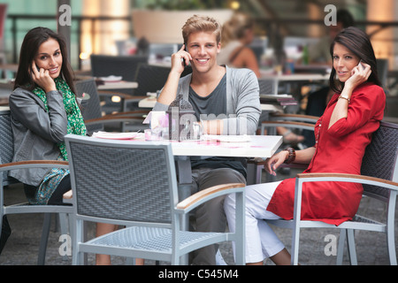 Three young friends talking on mobile phones in a restaurant - Stock Photo
