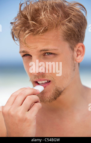 Young man applying moisturizer on his lips - Stock Photo