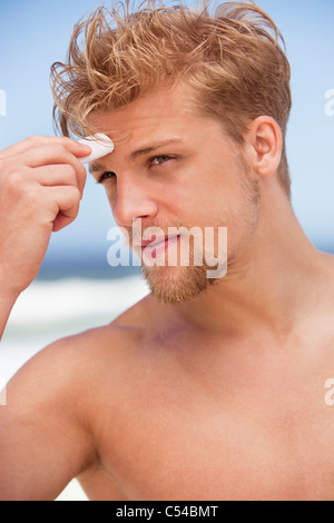 Young man applying moisturizer on his face - Stock Photo