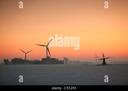 The Netherlands, Tritzum, Small traditional windmill, wind turbines and farm in snow at sunset. - Stock Photo