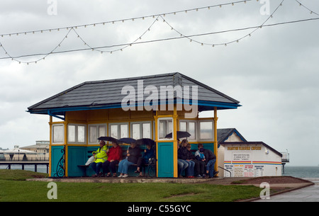 traditional British seaside holiday,People sheltering from summer rain in seaside shelter in Paignton,Devon,staycation,vacation - Stock Photo