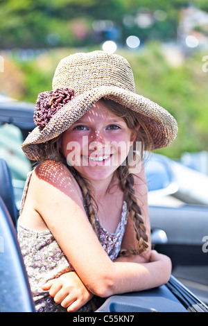 a seven-year-old girl in an open convertible in the summer - Stock Photo