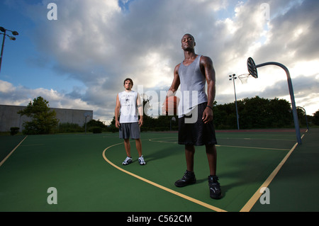 males after after playing basketball on outdoor court, dramatic sky - Stock Photo