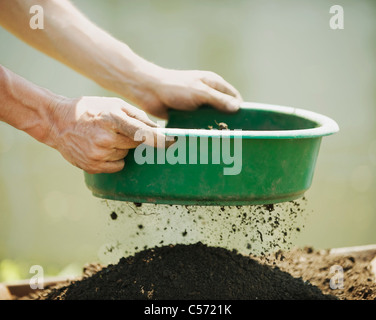 Hands sifting soil outdoors - Stock Photo