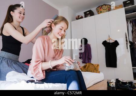 Teenage girl combing friend's hair - Stock Photo