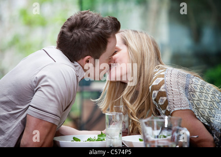 Couple kissing over meal at home - Stock Photo