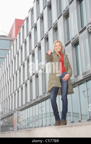 Woman giving a thumbs up on city street - Stock Photo