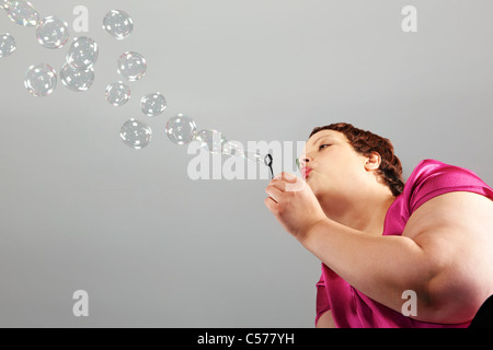 Large woman blowing bubbles - Stock Photo