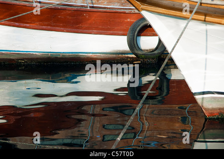 A small fishing boat on the shore and its reflections on the water - Stock Photo