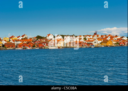 Mollösund fishing village at a distance against clear sky with sea in the foreground - Stock Photo