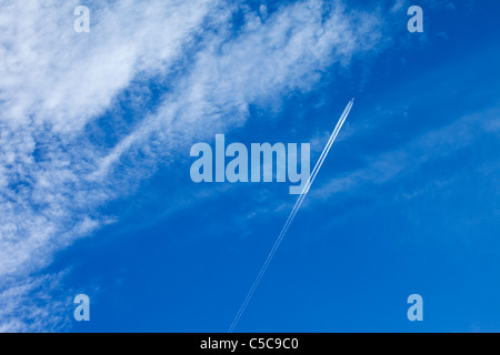 A passenger aircraft in Britain leaving vapour trails against a blue sky and high cloud - Stock Photo