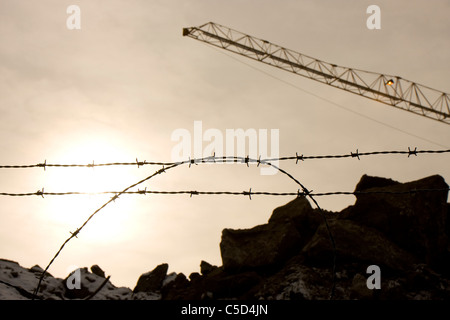 Close-up of barbed wire fence with rocks and crane against clear sky at construction site - Stock Photo