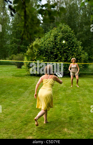 Two women playing badminton in the backyard against trees - Stock Photo