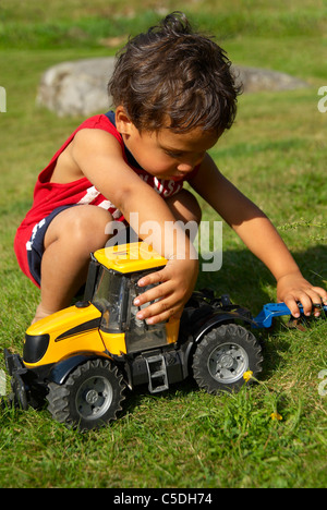 Little boy playing with a toy tractor on grass - Stock Photo