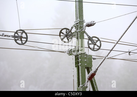 Close-up of electricity lines against the sky in winter - Stock Photo