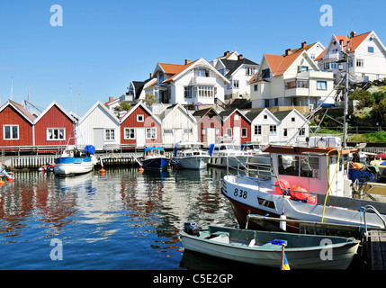 Boathouses against clear blue sky with moored boats in water in foreground at Ã…stol, Sweden - Stock Photo