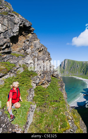 Female tourist on rocks enjoying the view of beach against blue sky and clouds in Norway - Stock Photo