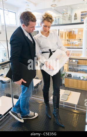 Full length of a male and female colleagues discussing architectural plan - Stock Photo