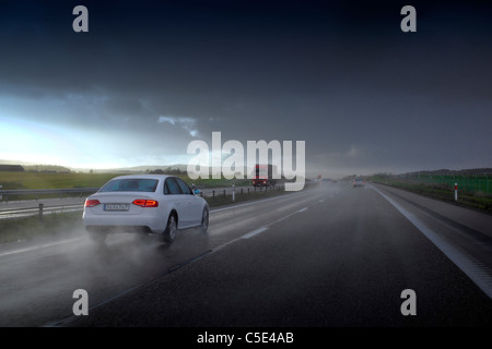View of vehicles on the asphalt road against cloudy sky on a rainy day - Stock Photo