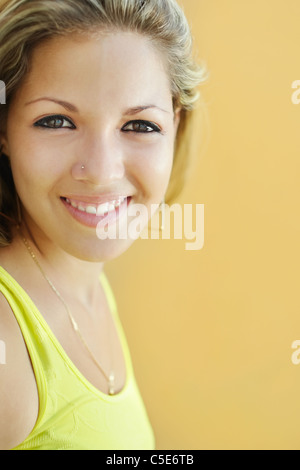 portrait of caucasian college student smiling and looking at camera with yellow wall in background. Selective focus, - Stock Photo