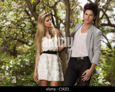 Young man and a woman in a garden standing under a blossoming tree, springtime scenic - Stock Photo