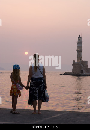 A mother and her daughter watch the setting sun over the entrance to Chania habour. Crete, Greece. - Stock Photo