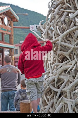 A young child exploring Jackson Hole's unusual Antler Gate. - Stock Photo