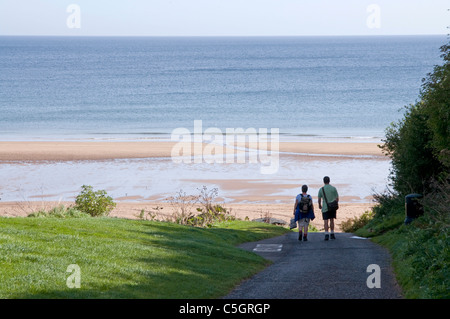 Couple walking down to Coldingham Bay - Stock Photo