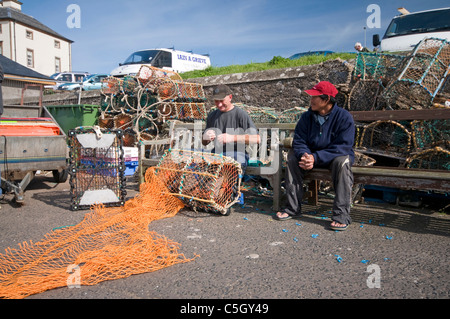 Fishermen mending nets on the harbourside at Eyemouth - Stock Photo