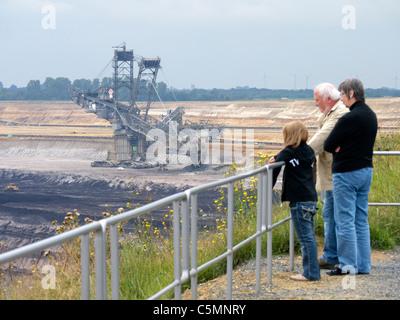 Visitors looking at RWE open-cast brown or lignite coal mine at Garzweiler in Northrhine Westfallia in Germany - Stock Photo