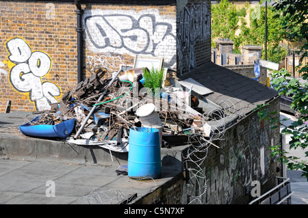 East London building and rubbish dump junk eyesore barbed wire on flat roof with graffiti painted on wall Hackney - Stock Photo