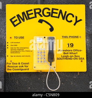 Wall mounted outdoor seaside emergency SOS telephone at Bell Wharf beside Thames Estuary Old Leigh on Sea Essex - Stock Photo