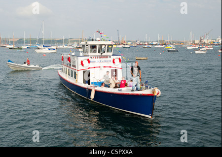 A small tourist boat returns to dock in Falmouth harbour after a tour of the quay. (Editorial use only). - Stock Photo