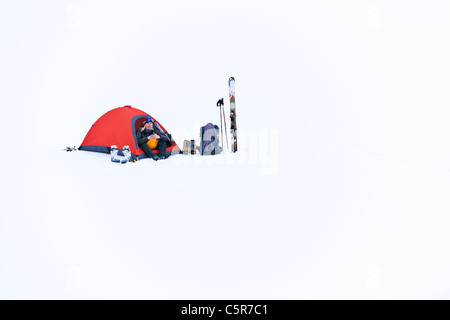 A women trying to keep warm sitting in her tent on mountain snow. - Stock Photo