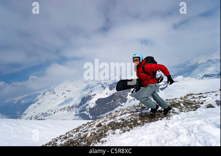 A snowboarder sprinting to be first to get the fresh lines. - Stock Photo