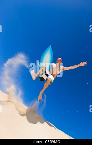 A surfer jumps of sand dune on way to Ocean. - Stock Photo